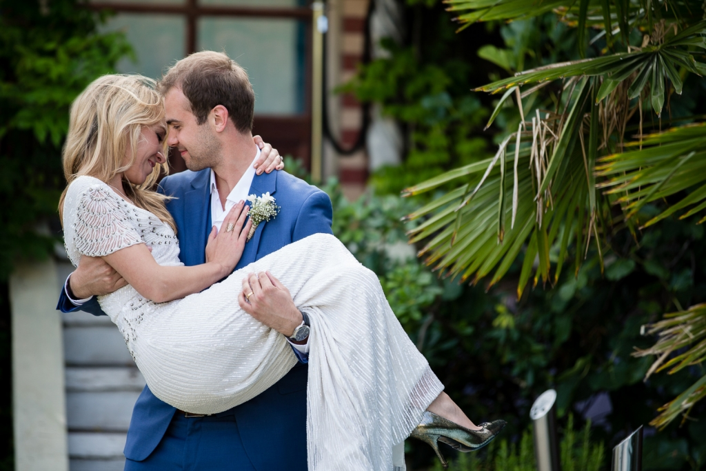 emotional bride with groom carrying - kensington roof gardens photography